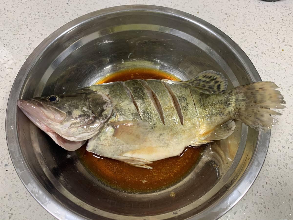在桂花鱼上划几刀,抹盐,倒入酱油,料酒腌10分钟左右。